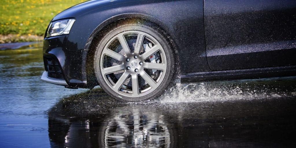 Автомобиль едет по мокрой дороге